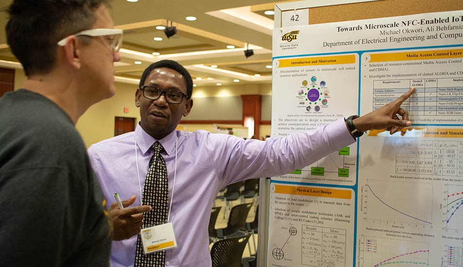 Wichita State University graduate student shares his research with a fellow student