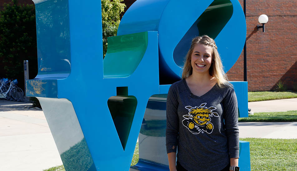 Wichita State Student Ali Phelps in front of the Love outdoor sculpture featured on campus