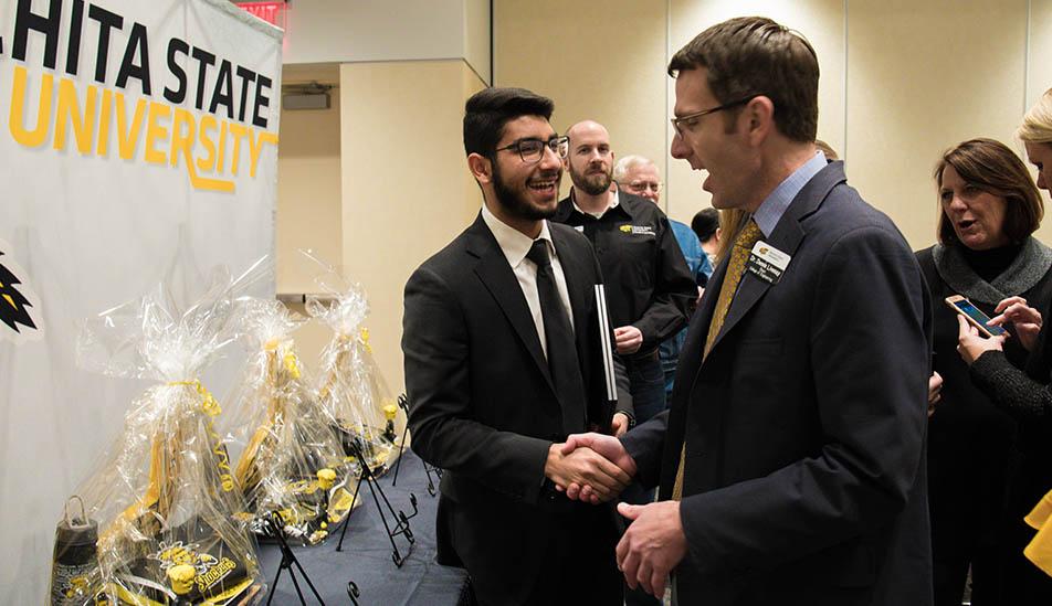 Gehad Qaki,Wichita State Gore Scholar receiving congratulations from Dean Livesay.
