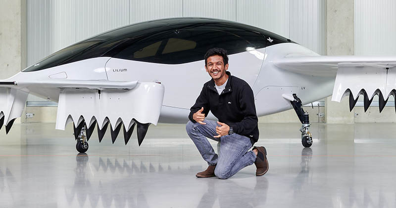 "Wichita State Alumni Aadhar Jain poses with a model of the ""Flying Taxi,"" an electric vertical takeoff and landing jet that his employer, Lilium, is developing."